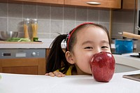 a girl in the kitchen eating apple