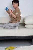 Boy reading book, side view