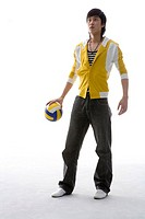 a fashionable man with a volleyball in his hand