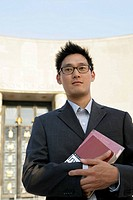 Asian man looking at camera holding books