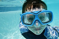 Little boy swimming, wearing goggles