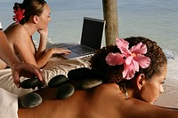 Women getting hot stone therapy massage and using laptop