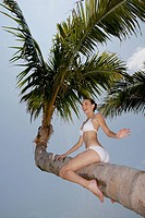 Happy young woman in palm tree
