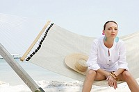 Young woman sitting in hammock on beach