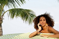 Young woman talking on phone at beach