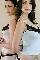 Two young women standing back to back (thumbnail)