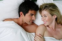 Young happy couple relaxing in bed