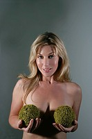 Topless woman holding grass balls over breasts
