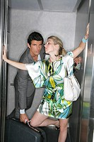Sexy woman blocking elevator door with man behind
