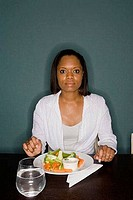 Portrait of a young woman sitting by table with a plate of vegetables