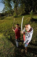 Portrait of friends playing with sword and stick at forest