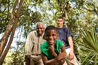 Portrait of a mature man with his son and friend smiling at forest