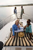 Portrait of smiling friends gesturing and relaxing on the deck of a boat