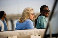 Smiling mid adult women wearing sunglasses and looking away