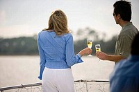 Rear view of a mid adult couple standing with glass of champagne