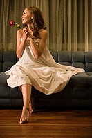 Young prostitute holding a rose while sitting on a sofa