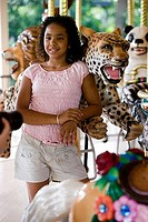 Teenage girl standing in a carousel by a carousel leopard