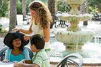 Young woman with girl and boy by water fountain