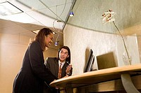 Businessman and businesswoman looking at a computer monitor in an office