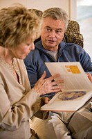 Mature couple holding a book and talking