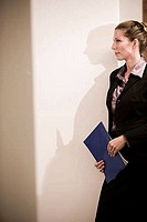 Businesswoman holding a file and leaning by wall in an office