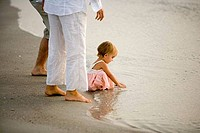Girl playing in water with parents standing beside at beach