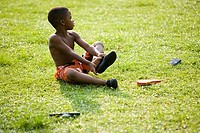 Boy sitting on grass and removing flip_flops