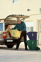 Daughter and father loading items for the recycling center into their car.