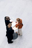 Overhead view of people standing with documents