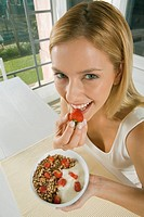 Happy woman eating cereal with strawberries