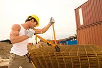 Side profile of a male construction worker cutting iron rods with a bolt cutter