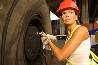 Close_up of a mid adult woman tightening the bolt of a tire