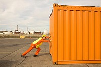 Side profile of a male dock worker pushing a cargo container
