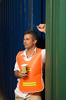 Dock worker holding a disposable cup