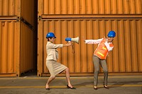 Businesswoman aiming a megaphone at a dock worker