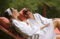 Two young women in bathrobes and reclining on lounge chairs in a health farm