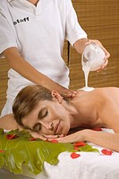 Mid section view of a massage therapist pouring moisturizer on a young woman's back