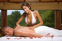 Side profile of a mature man receiving a back massage from a young woman massage therapist (thumbnail)