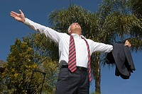 Low angle view of a businessman standing with his arms outstretched