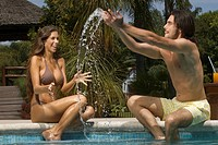 Young man sitting beside a young woman and splashing water from the poolside