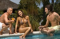 Young couple and a mature man at the poolside