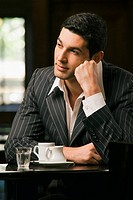 Close_up of a young man sitting in a restaurant and thinking