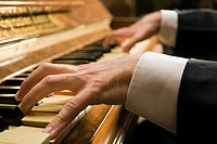 Close_up of a man's hands playing a piano