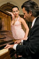 Woman looking at a man playing a piano