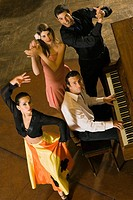 High angle view of a young couple clapping beside a man playing piano and a woman dancing