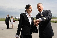 Pilot and a cabin crew checking the time with a businessman walking in the background