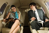 Businessman and a businesswoman sitting in a private airplane