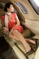 Businesswoman looking out of the window in a private airplane