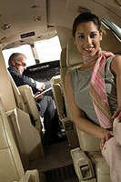 Portrait of a businesswoman smiling with a pilot sitting in the background