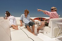 Family relaxing on boat with father pointing into distance